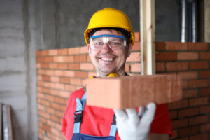 Happy builder holds brick for masonry and smiles.
